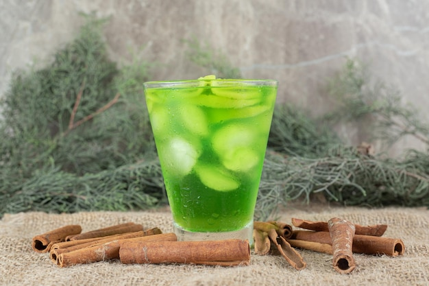 Un bicchiere di succo di kiwi e bastoncini di cannella su tela