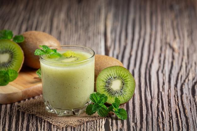 Bicchiere di succo di kiwi messo sul pavimento di legno