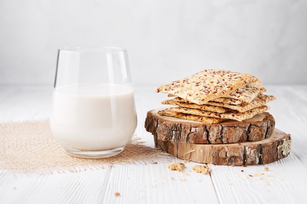 The glass of lactose free vegetable milk: soy, rice, oat or almond milk and biscuits with sesame seeds