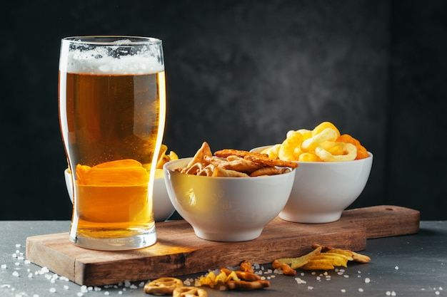 Glass of lager beer with snack bowls on dark stone