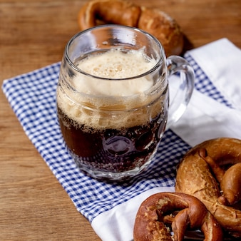 Glass of lager beer with traditional salted pretzels on white and blue napkin over wooden background. oktoberfest theme. square image