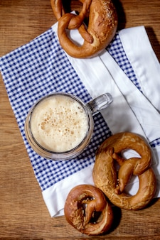 Glass of lager beer with traditional salted pretzels on white and blue napkin over wooden