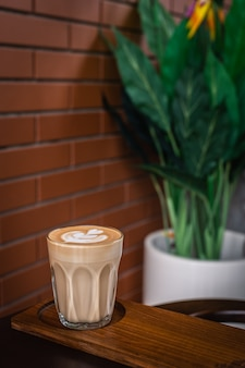 A glass of latte art on wooden plate with brick wall