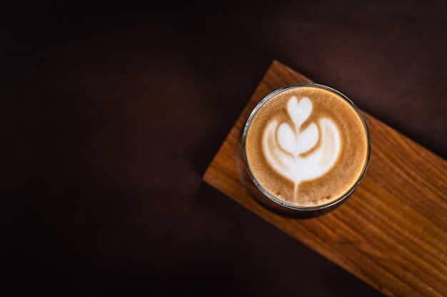 A glass of latte art on wooden plate on wooden board
