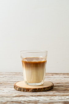 Glass of latte coffee, coffee with milk on wood background