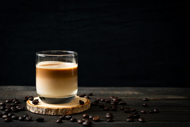 Glass of latte coffee, coffee with milk on wooden table