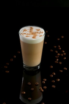 Glass of latte coffee with beans on black background
