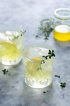 Glass of lemon fresh summer drink in glass. soda lemonade drink with herb.