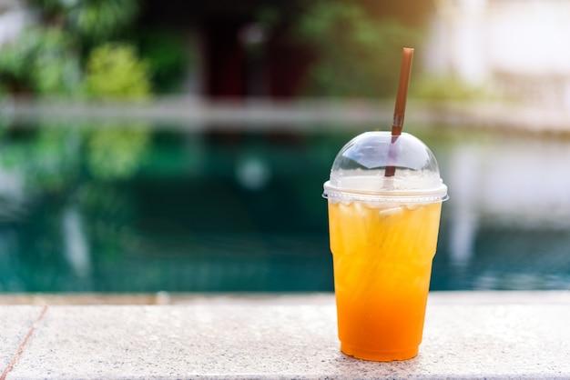 A glass of lemon honey soda juice on swimming pool.