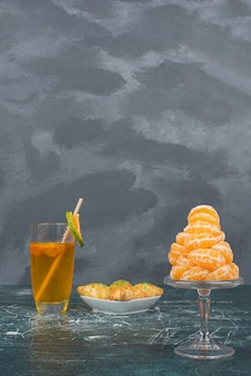 Glass of lemon water with plate of sweet bakery and slices of tangerine .