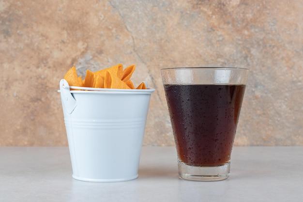 Bicchiere di limonata e secchio di patatine a forma di triangolo.