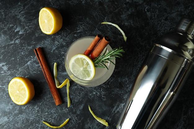 Glass of lemonade with cinnamon and rosemary on black smokey table