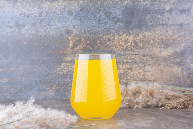 Glass of lemonade with ears of wheat on marble table. high quality photo
