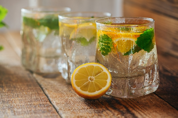 Glass of lemonade with fresh lemon and mint on wooden background