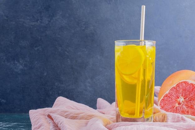 Un bicchiere di limonata con fette di limone e pompelmi sulla superficie in marmo.