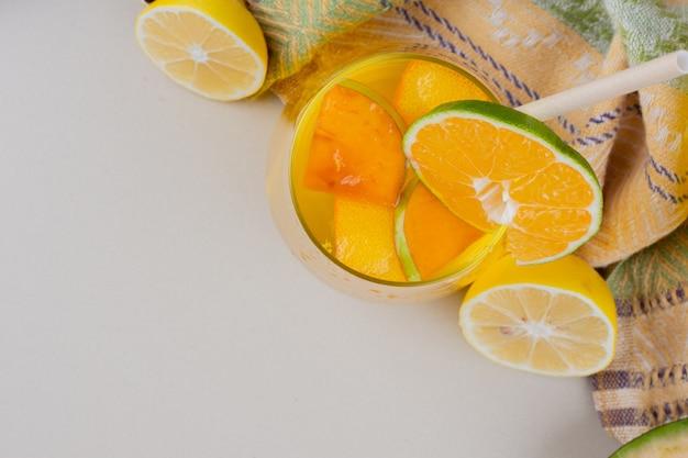 Un bicchiere di limonata con fette di limone sulla superficie bianca.