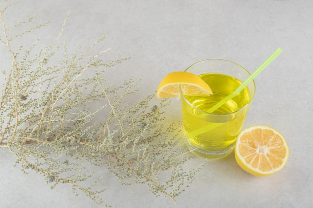 A glass of lemonade with lemon and straw on gray surface