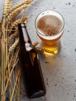 Glass of light beer and beer bottle on wooden background