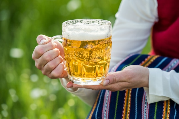 Glass of light beer in the hands of woman.