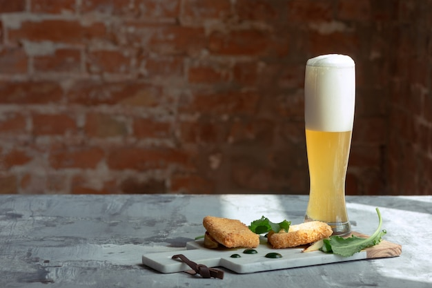 Glass of light beer on the stone table and bricks wall.