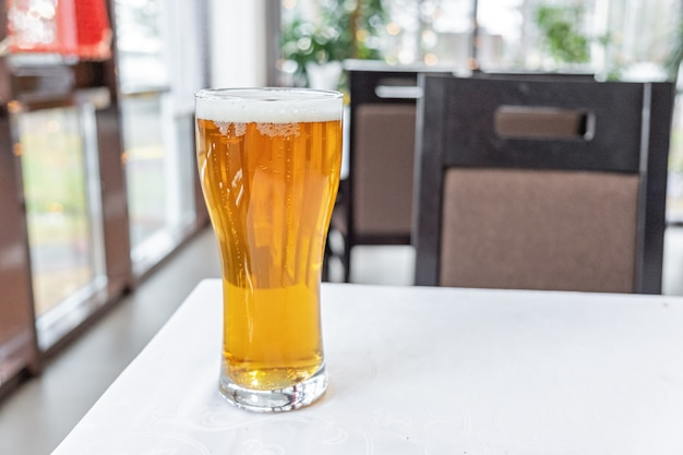 Glass of light beer on a table in a bar