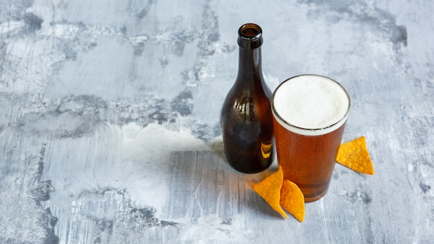 Glass of light beer on white stone surface