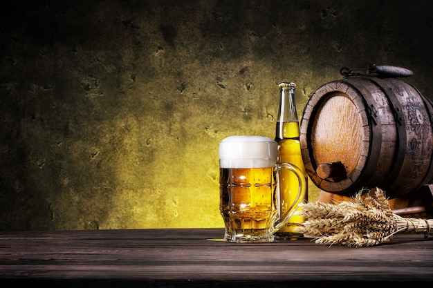 Glass of light beer with bottle and barrel