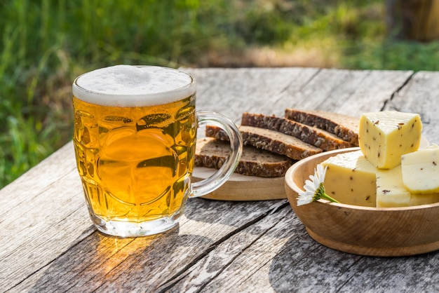 Glass of light beer with cheese and rye bread