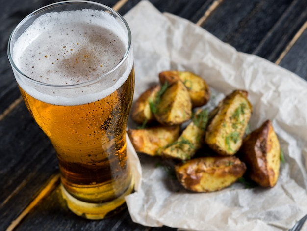 A glass of light beer with a snack in the form of rustic potatoes with dill on a dark wooden background