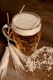 Glass of light beer with spike barley on wooden table