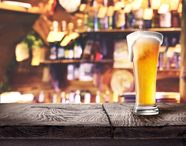 Glass of light beer on wooden board
