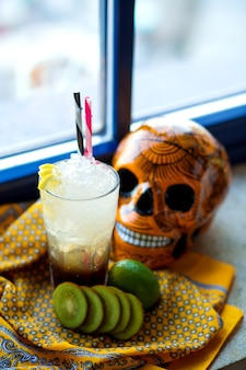 A glass of lime and kiwifruit cocktail next to orange mexican skull