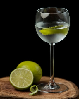 Glass of lime water with lime zest on wood serving board
