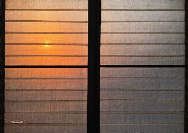 Стеклянные жалюзи и противомоскитные сетки с оранжевым светом от заката.