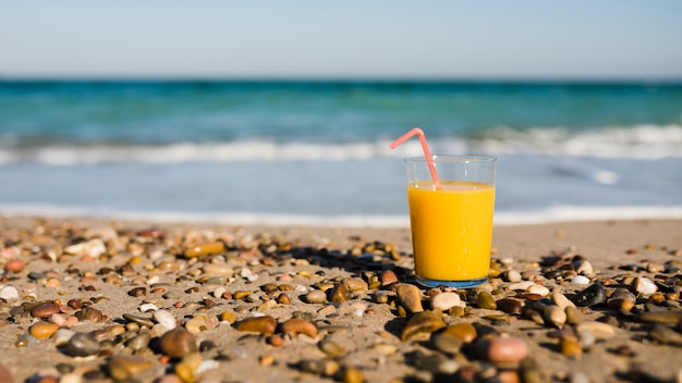 A glass of mango juice with drinking straw on sand at beach