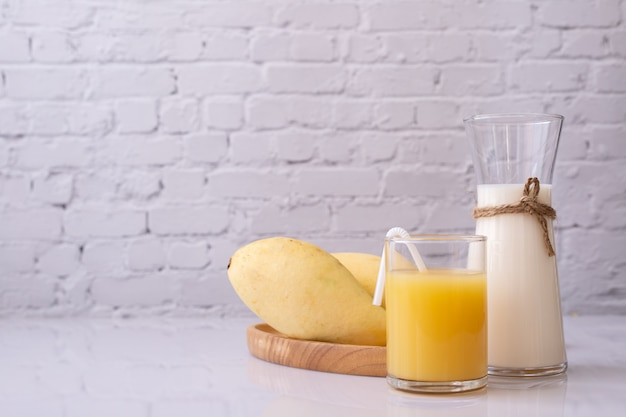 Glass of mangoes juice and milk jug on table.