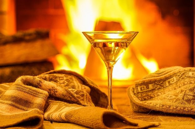 Glass of martini against cozy fireplace background