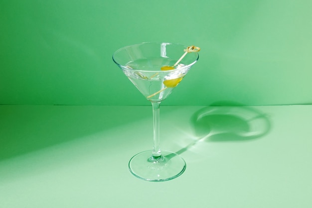 Glass of martini cocktail with green olives. focus on shadows