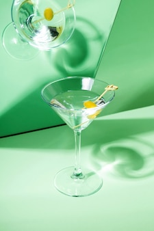 Glass of martini cocktail with green olives reflected in mirror. focus on shadows