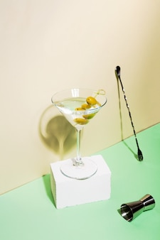 Glass of martini cocktail with green olives on white pedestal nearby jigger and bar spoon