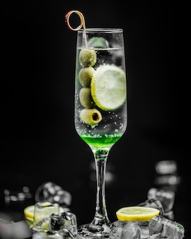 A glass of martini with olives and lemon slice.