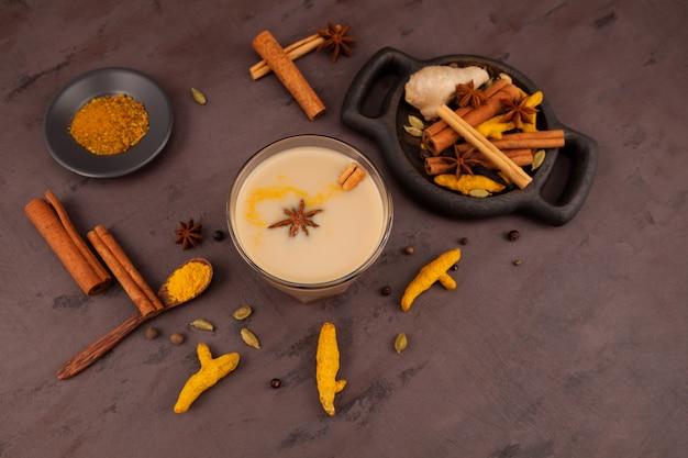 Glass of masala tea or karak chai. set ingredients for popular indian drinks.