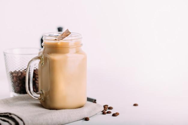 Glass mason jar with ice coffee with milk background