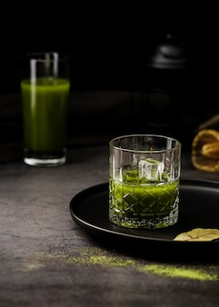 Glass of matcha tea with ice cubes