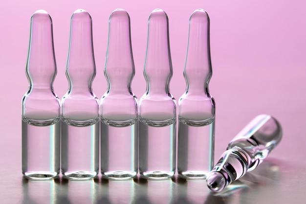 紫ピンクの背景に透明な液体とガラスの医療アンプル