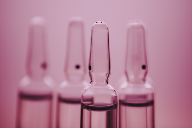 Glass medicine ampoules on a pink wall close up