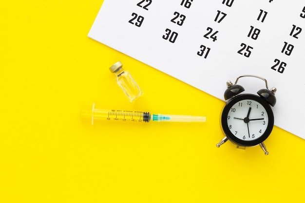 Glass medicine vial with liquid and syringe, calendar and alarm clock on yellow background. medical vassination schedule. health concept. flat lay, top view with copy space.