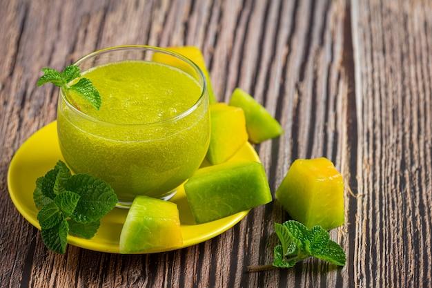 Glass of melon juice put on wooden floor