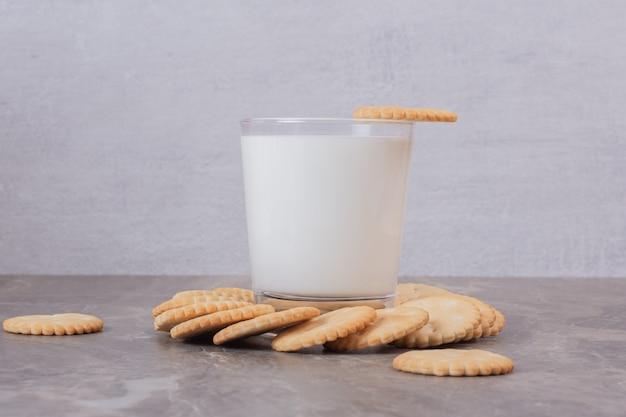 Tavolo in marmo bicchiere di latte e biscotti.