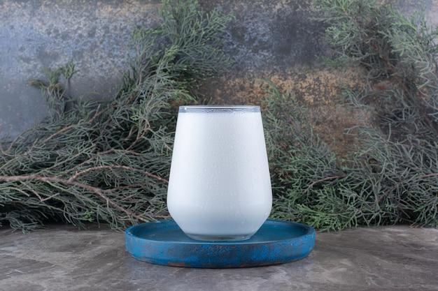 Bicchiere di latte sul piatto blu con ramo di pino. foto di alta qualità